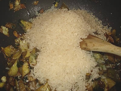 Aggiunta riso nella padella coi carciofi